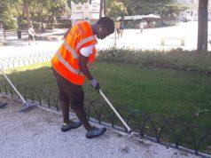 Un migrante impegnato nella pulizia di un'area verde della città