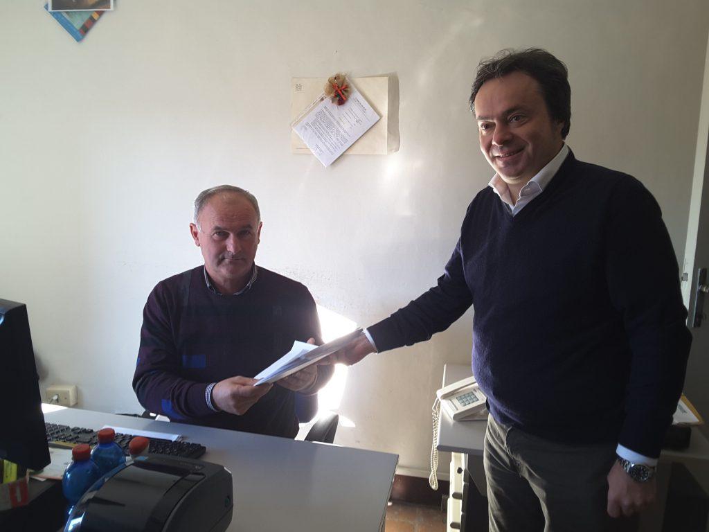 Andrea Pieralisi mentre consegna la petizione all'addetto dell'ufficio protocollo, Angelo Costarelli