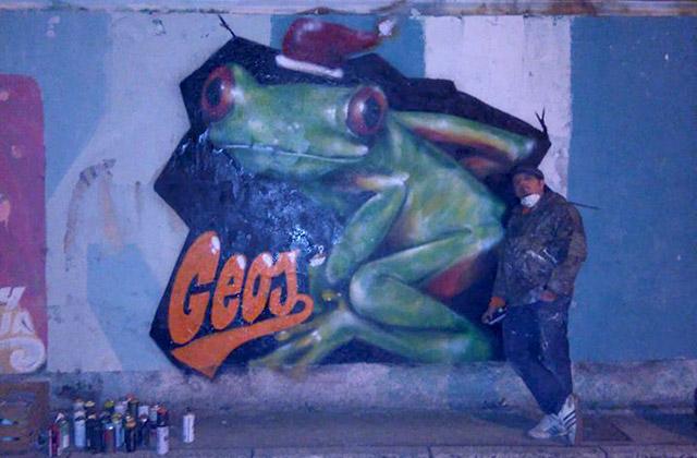 Michele Droghini, in arte Geos, a fianco di uno dei suoi graffiti