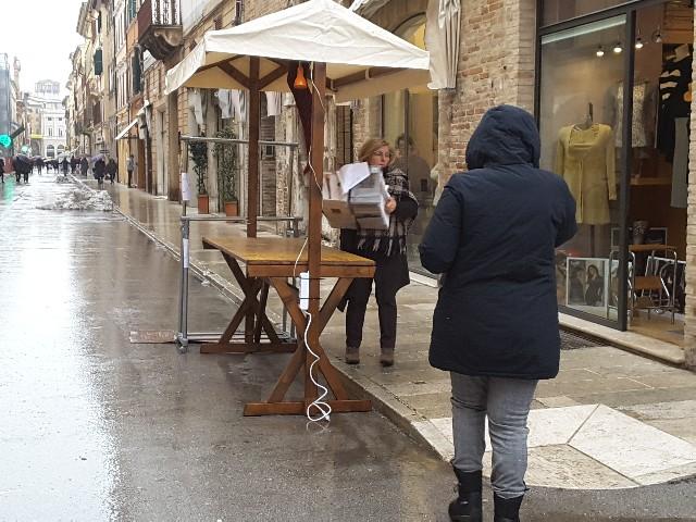 Si toglie la merce esposta sul banchetto a causa della pioggia