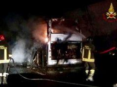 L'autobus avvolto dalle fiamme con i vigili al lavoro