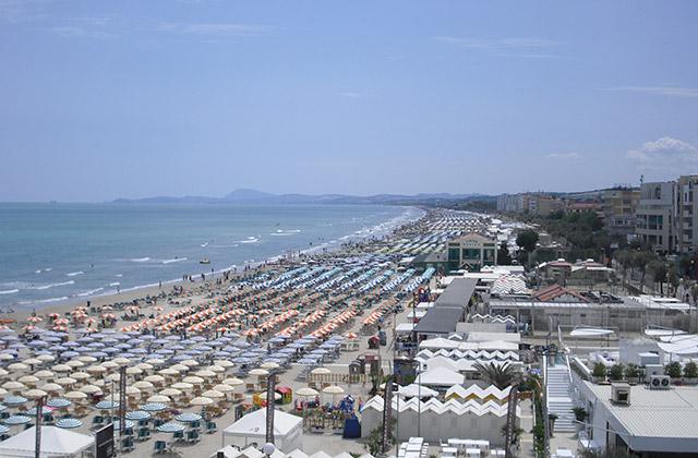 L'estate a Senigallia: una distesa di ombrelloni sulla spiaggia di velluto con vista del Conero