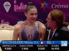 Milena Baldassarri abbracciata dall'allenatrice Kristina Ghiurova mentre la tv israeliana mostra il primo posto al Nastro dell'atleta azzurra