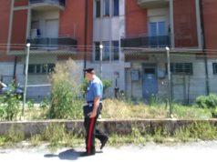 I carabinieri sul posto. Nello sfondo il palazzo dove è stata trovata senza vita la donna