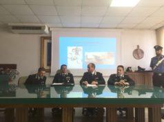 I carabinieri mentre illustrano i dettagli dell'arresto, sullo sfondo i gioielli della vittima e il coltello sequestrato in casa
