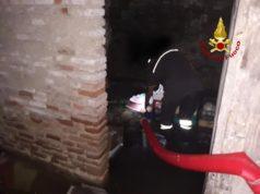 Un vigile al lavoro con la pompa usata per contrastare l'allagamento