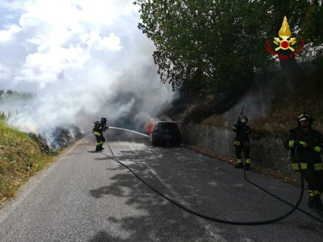 I vigili spengono le fiamme che partite dal motore dell'auto hanno coinvolto anche la scarpata