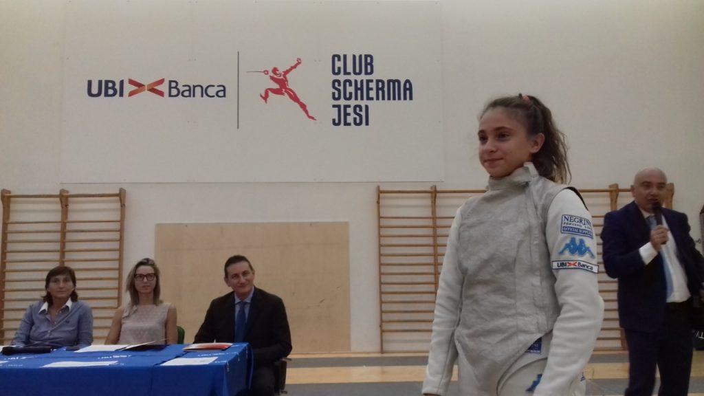 Sofia Giordani mostra la nuova divisa Ubi Scherma Jesi, dietro ci sono Nunzio Tartaglia, Valentina Vezzali e Giovanna Trillini