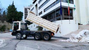 Il camion scarica la neve davanti alla Regione