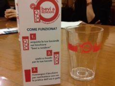 """Il bicchiere in plastica lavabile e riutilizzabile e il materiale informativo dell'iniziativa """"Bevi a rendere"""""""