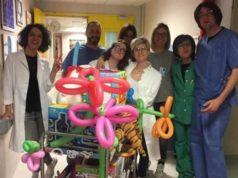 A destra il dottor Popozzi insieme al suo carrello carico di giochi, alla dottoressa Cannarozzo, medici infermieri e membri del Comitato Genitori Bambini Cardiopatici con la presidente Valentina Felici