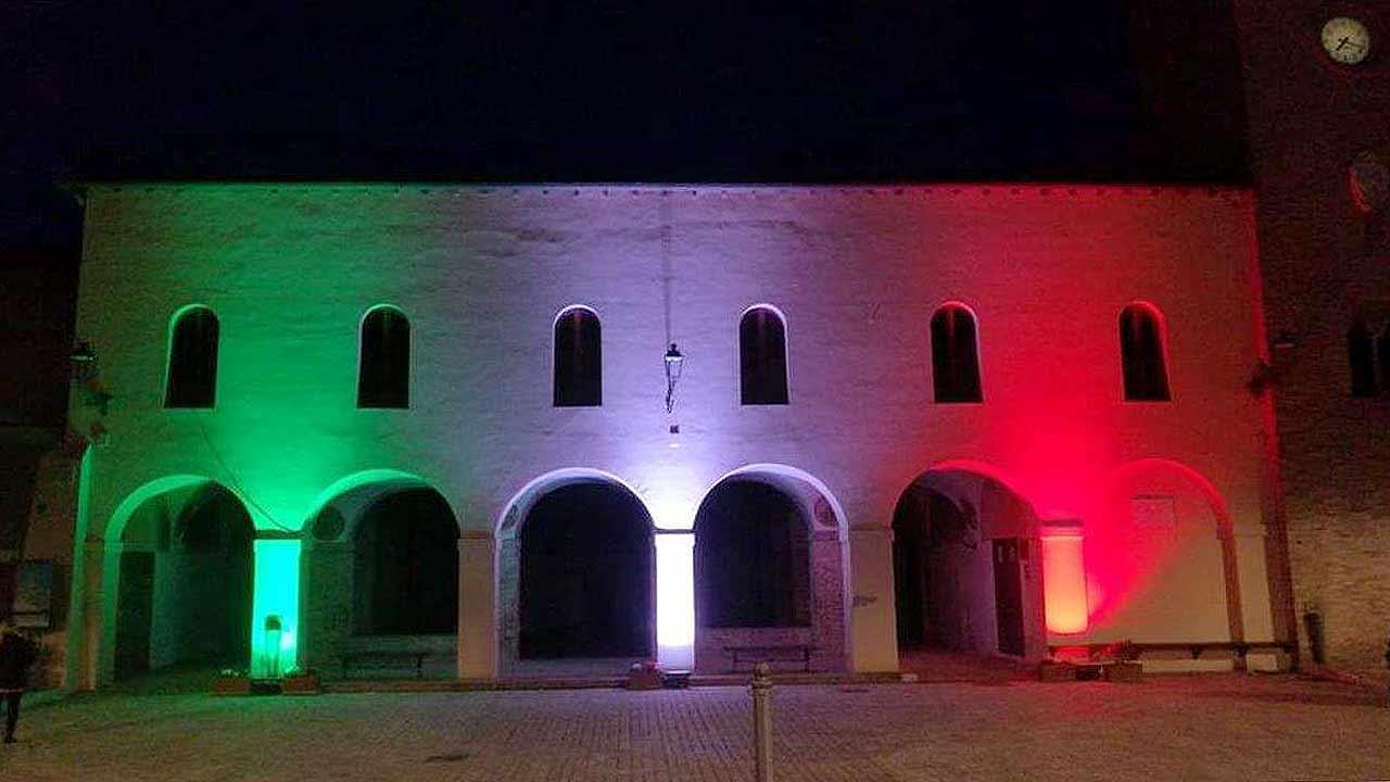Il tricolore illumina la facciata dell'ex convento San Francesco al Mercatale, nella centrale piazza della Libertà a Ostra Vetere